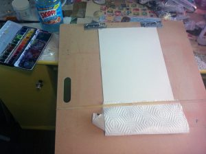 Here's my setup. I'm using hot pressed 140lb watercolour paper. I almost always use this paper for drawing because it's sturdy and can handle all media.  Bristol would also work for this as it can handle watercolors to a point as well (you might just need to flatten it out afterwards if it gets too warped).  I've got it set up at an angle (gravity is your friend for this technique) and paper towel ready to absorb any extra paint.