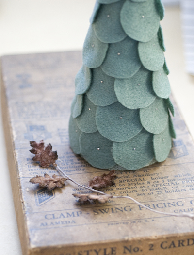 Next is this felt shingle style tree.  The base is floral foam in a cone shape (the green stuff you can get at Michaels or any craft store).  The shingles are simple circles cut out of felt and pinned to the cone.  Simple, cute, and they can be any colour you need to fit your holiday colours!