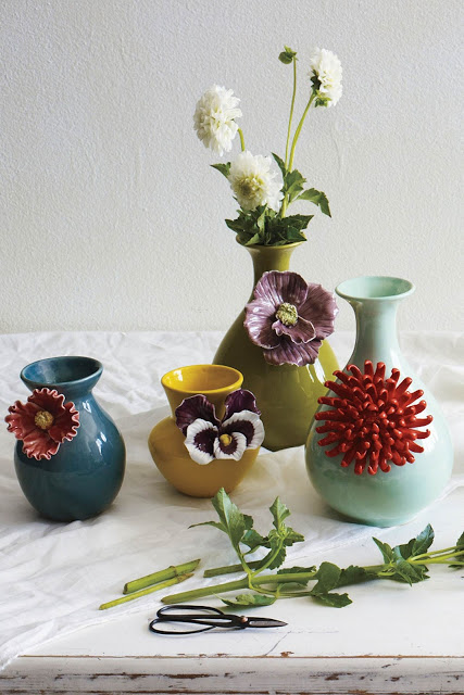 These cute vases are as easy a gluing a clay flower onto a dollar store vase...literally.