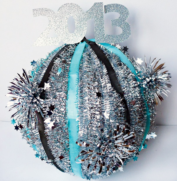 Recreate the ball drop at home with this cute tinsel ball! It's just a styrofoam sphere with garland wrapped around it, but looks so festive.